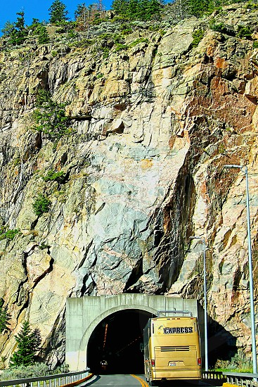 Tour bus on the highway goes through a tunnel in a tall rocky mountain photo