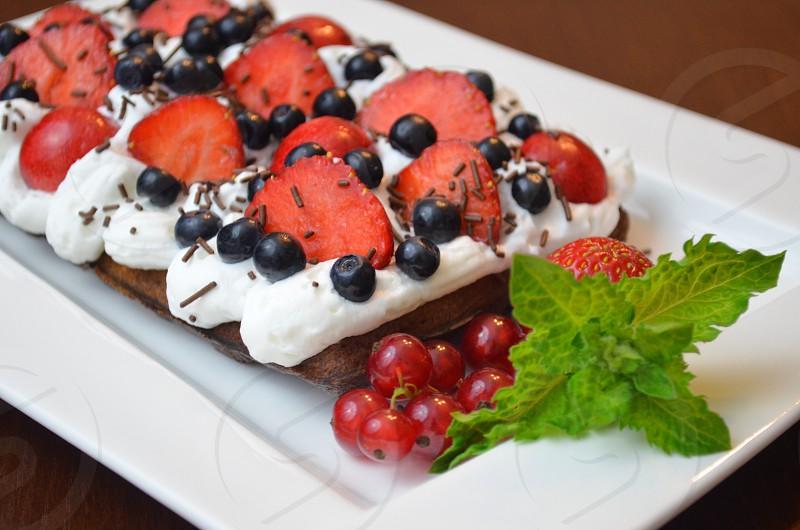 Fruit strawberries blueberries whipped cream waffle chocolate  photo