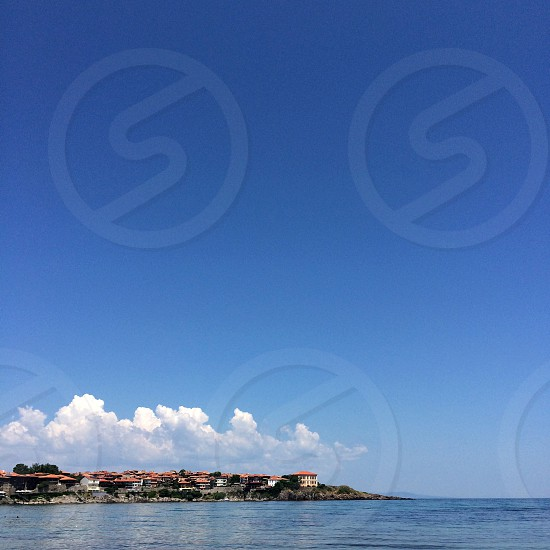 white brown houses across body of water under clear blue sky photo