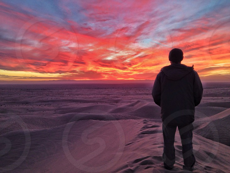 man wearing a grey jacket standing in sand looking towards a sunset photo