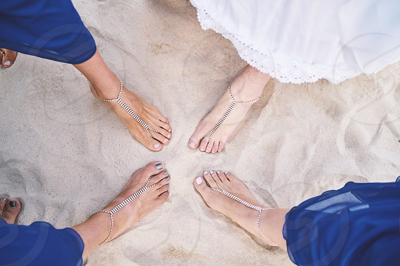 Bridal party play on the beach Bride and bridesmaids show feet with bracelets on the white sand photo