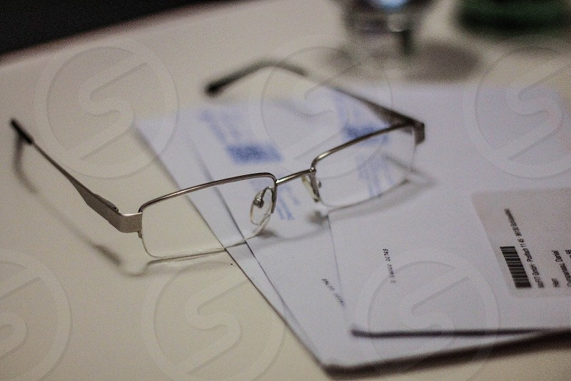 gray framed eyeglasses on top of white paper photo