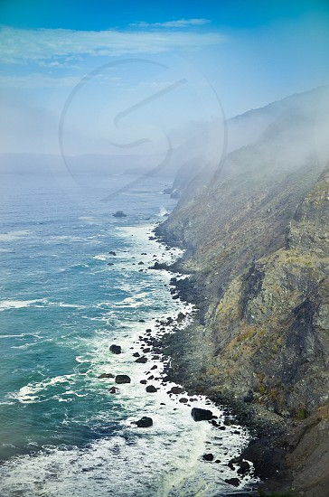 Green cliffs by the ocean under hazy sky photo