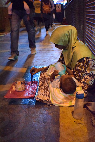 Spotted a poor woman feeding her baby while doing her routine task as a beggar. photo