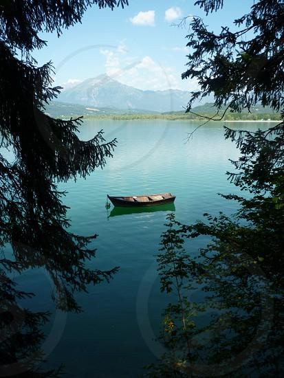 brown wooden row boat drifting at the lake photo