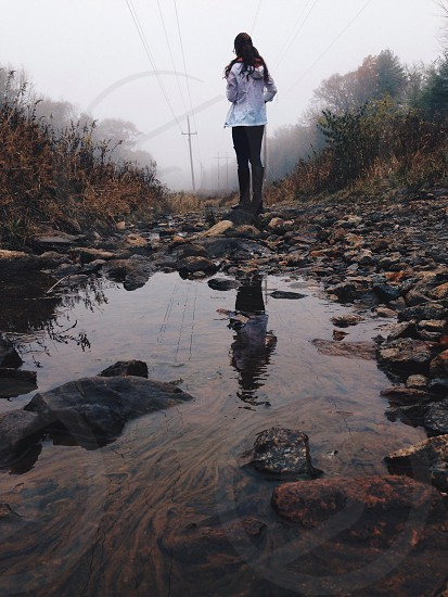 woman walking over puddles and rocks on a misty day photo