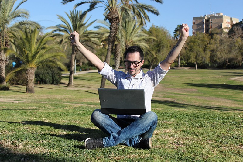 man wears white sports shirt using grey laptop computer seats on green grass photo