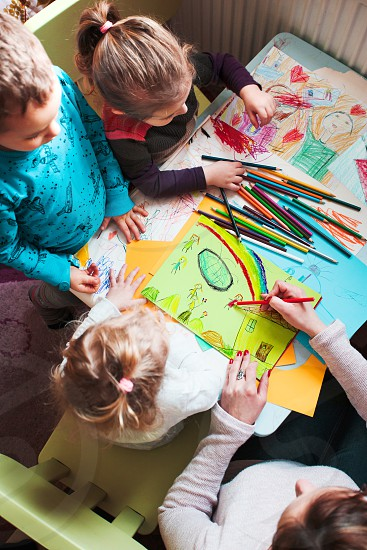 Mom with her little daughters and son together drawing a colorful picture of playing children using pencil crayons sitting at table. Photo from above photo