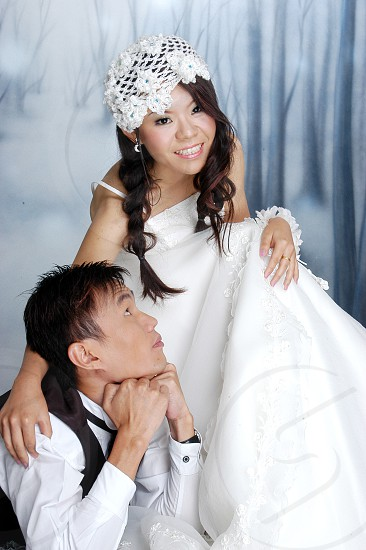 woman with white spaghetti strap floral wedding gown with floral head accessory sitting on a chair beside a man with white torso shirt and black vest looking up towards the girl photo
