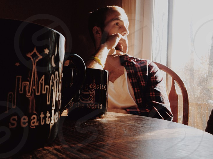 man sitting at table with seattle coffee mugs photo