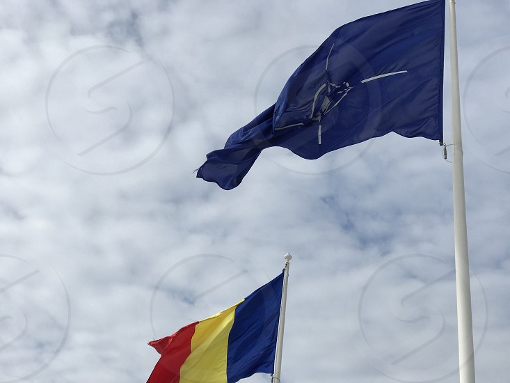 Romanian and NATO flags blowing in the wind photo