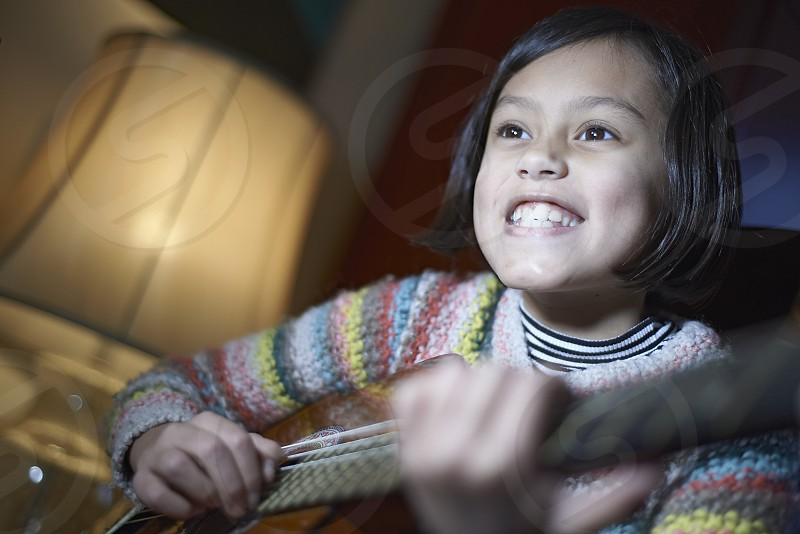 Cute young mixed race girl holding her acoustic guitar and happily smiling into camera photo