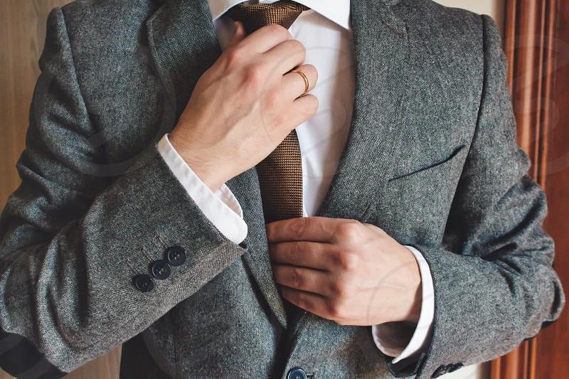 Man in smart suit wearing wedding ring adjusting tie photo
