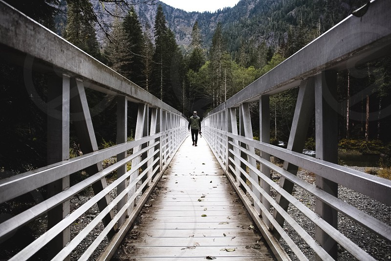person standing on white gray wood walkway photo