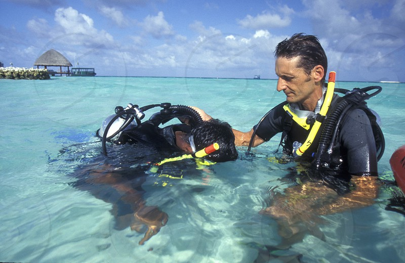 Divers on a beach with the seascape of the island and atoll of the Maldives Islands in the indian ocean. photo
