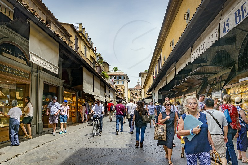 Florence Italy June 2015: tourists and Florentines walking along the famous Ponte Vecchio with its famous jewelers shops photo
