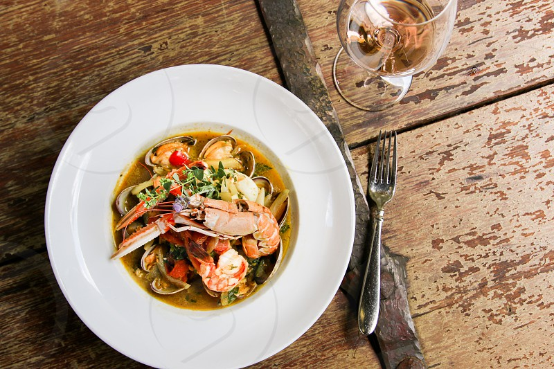 Seafood and rose wine on antique table overhead photo