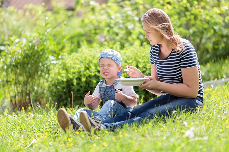 Cute little boy being fed outdoors on the grass by his mother reacting unfavorably to the food pulling a comical face photo