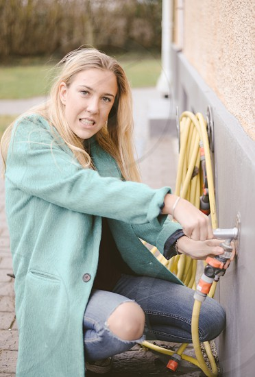 woman in teal coat squatting by a yellow garden hose during daytime photo