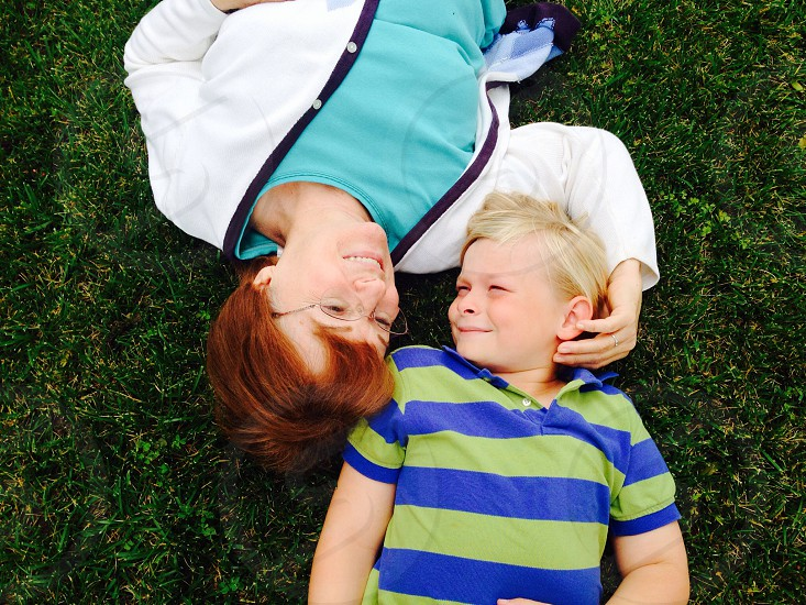 woman with short red hair lying next to boy with blond hair in blue and green striped polo shirt photo