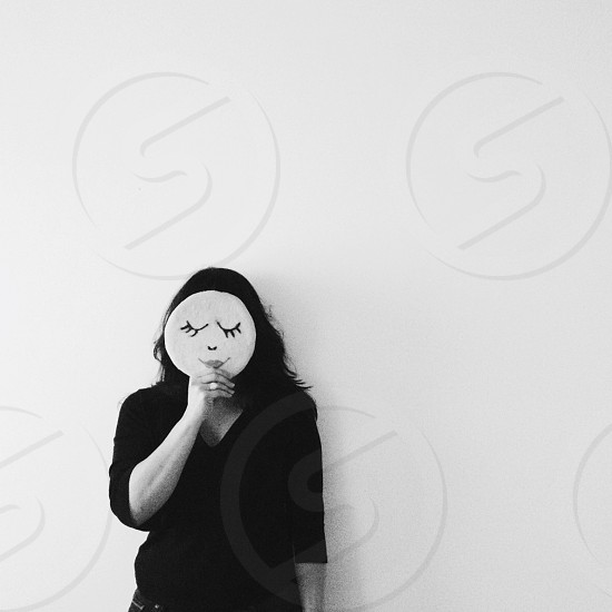woman in black sweater holding mask in front of her face photo