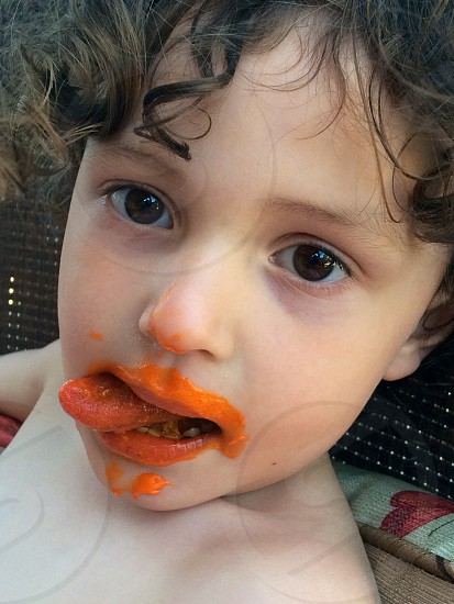 brunet curly-haired child with orange sauce on its face photo
