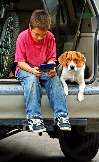 A beagle dog sits next to a boy in an open hatch which the boy plays a game. photo