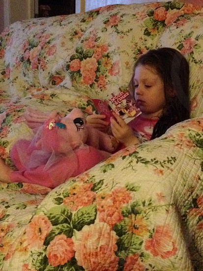 Child reading a book in a quilt photo
