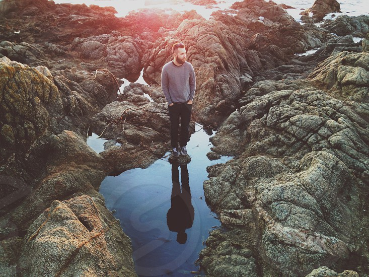 man standing in tidepool photo