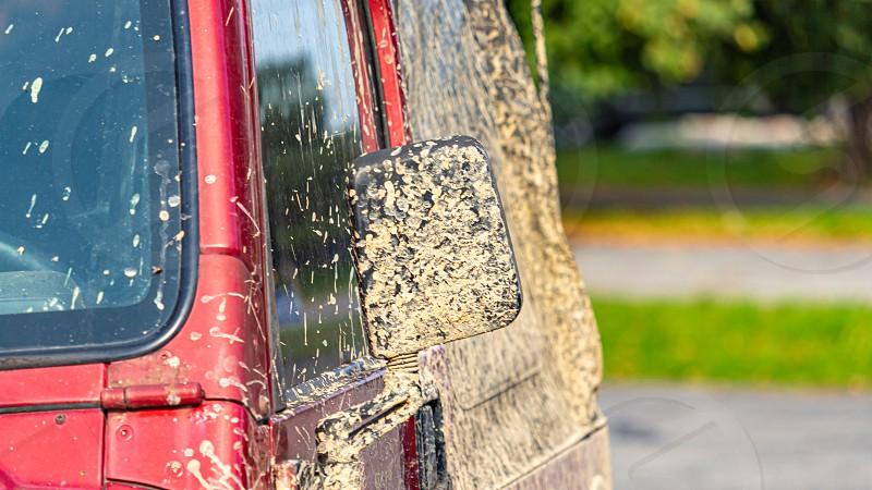 A vehicle capable of off-road driving is covered in caked mud from a drive through dirt roads. photo
