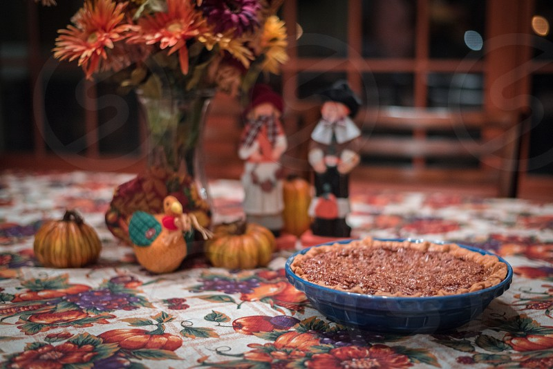 Pecan pie sitting on a table that is set for Thanksgiving Day. Pilgrims and fall colored centerpiece in the background. photo