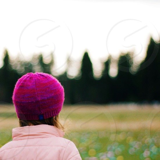 girl in pink knit hat standing in field photo