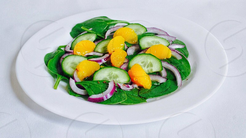 mandarin salad with green spinach red onions and sliced cucumbers on a white round plate photo