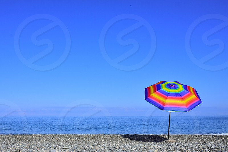 red yellow blue beach umbrella near the seashore under clear blue sky during daytime photo