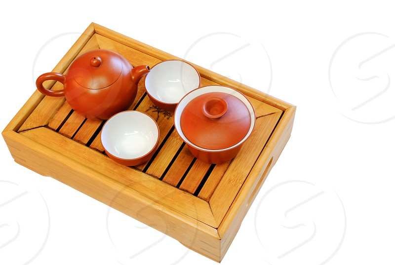 The oriental tea set on a bamboo tray isolated on white background. photo