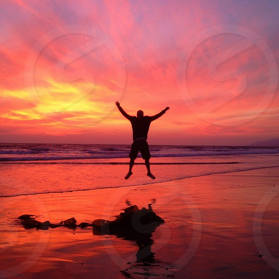 man jumping under sunset silhouette view photo