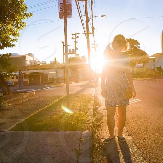 woman standing on roadside behind sun rays photo