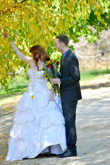 man in black suit and woman wearing a white wedding dress photo