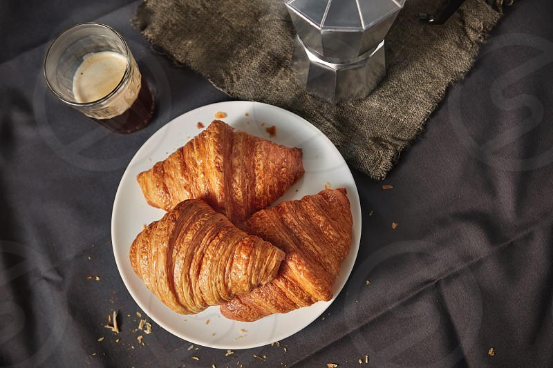 Top view of continental morning breakfast with homemade delicious french croissants on a plate and freshly brewed aromatic coffee on a dark textile copy space. photo