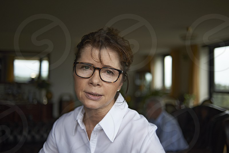 Elderly woman in her home wearing spectacles looking worried photo