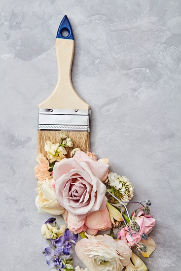 made of flowers with paint brush on stone background. Flat lay photo