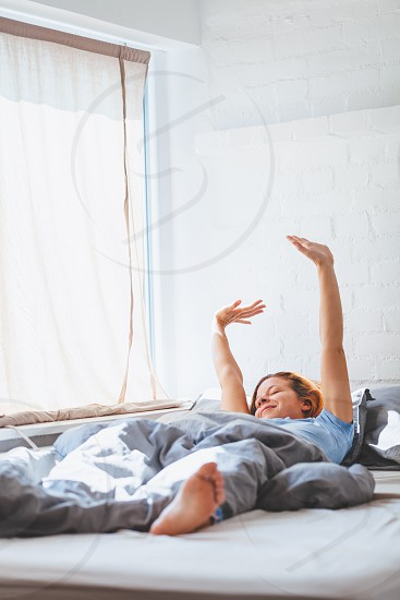 Young woman waking up lying in the bed photo
