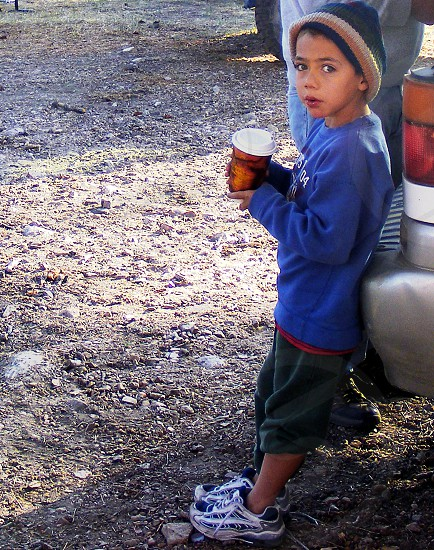A little boy at a campsite wearing a warm cap leans against a car and holds a hot drink. photo