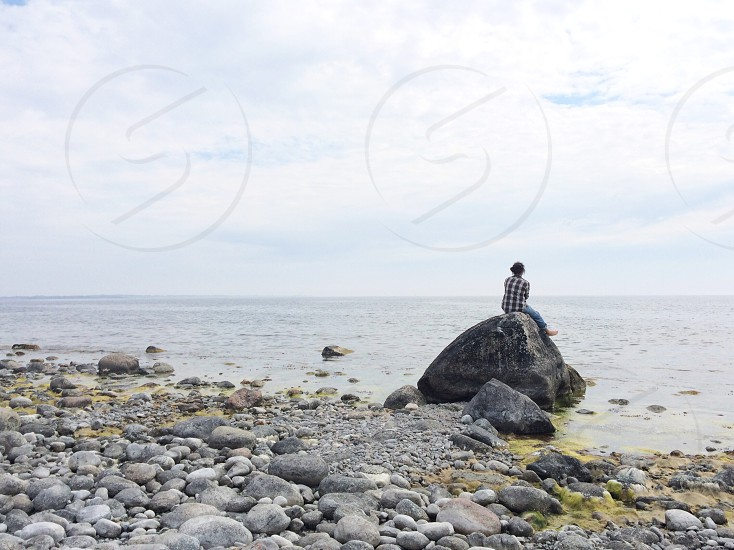 person sitting on gray rock stone by the shore photo