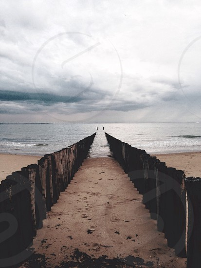 brown beach and ocean water under white clouds photo
