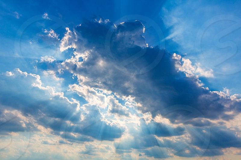 Dramatic cloudy sky clouds with real sun beams background photo