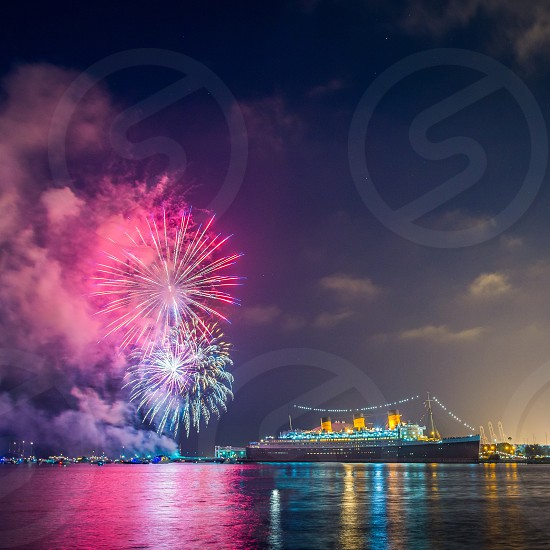 lighted cruise ship in a harbor with a pink and white fireworks display in teh sky photo