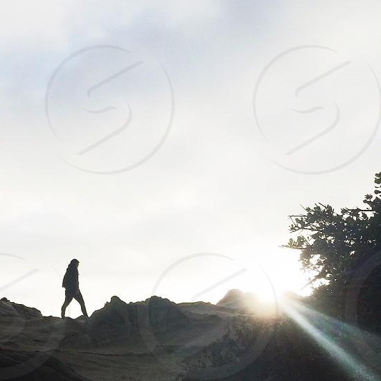 woman walking on hilltop photo