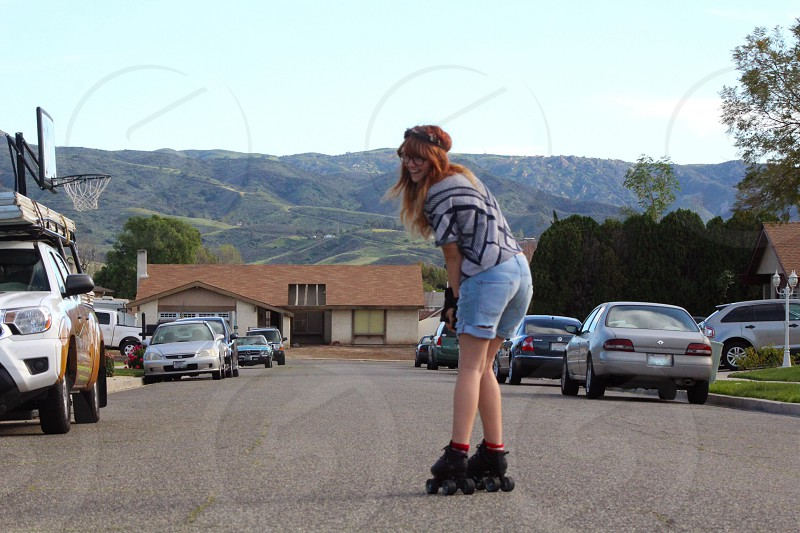 woman wearing black and gray top and blue denim shorts on gray asphalt road at daytime photo