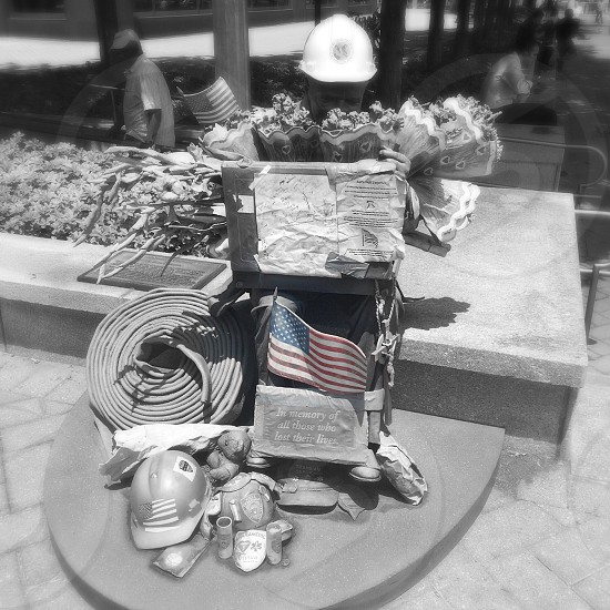 grayscale photography of firefighter memorabilia on gray concrete surface photo